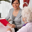 A young woman reads to seniors from a book