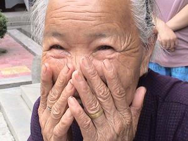 Happy embarrassed elderly woman at senior home in China
