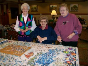 Jigsaw as a group game for seniors - seniors at jigsaw table