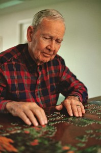 Jigsaw puzzles as a brain exercise - senior man solving a puzzle