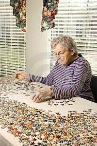 Jigsaw puzzles for seniors - elderly woman solving a complex jigsaw