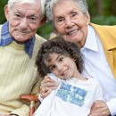 Portrait of a child with his grandparents outdoors