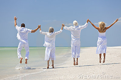 Seniors and family having fun and jumping in celebration on a tropical beach