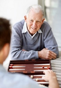 Backgammon Brain Games for Seniors Senior Man playing backgammon with young man